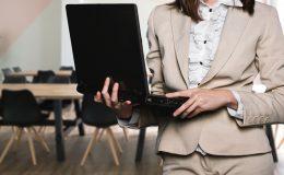 femme en tailleur beige avec ordinateur portable