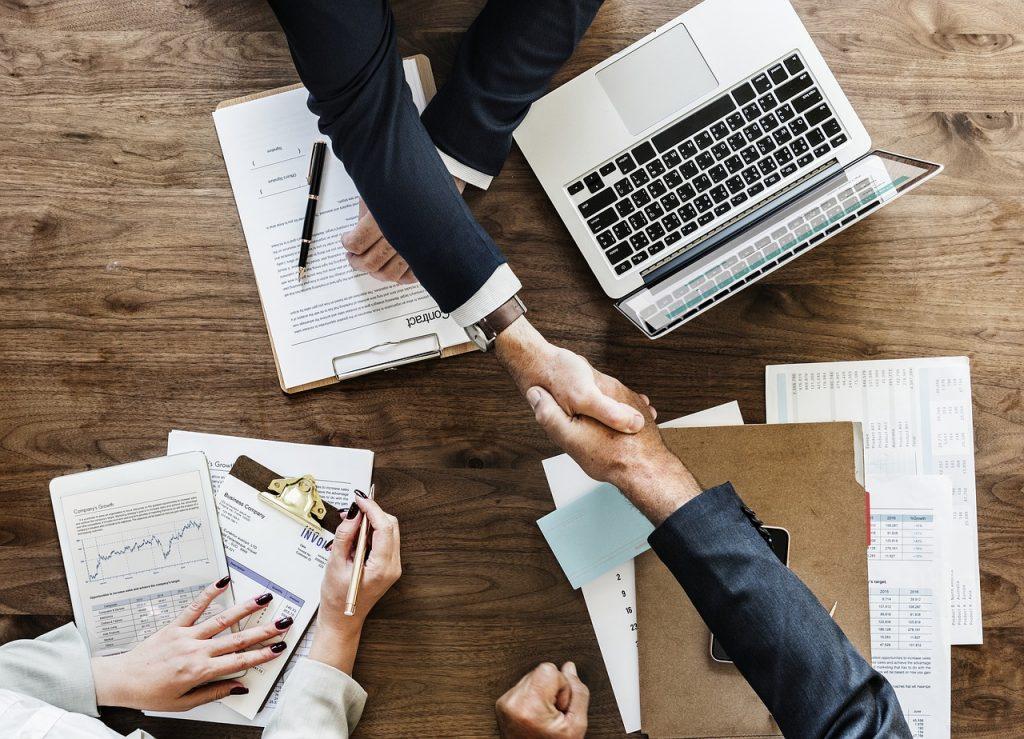 Hommes d'affaires qui se serrent la main par-dessus un bureau