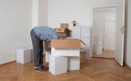 homme penché en avant la tête dans cartons de déménagement