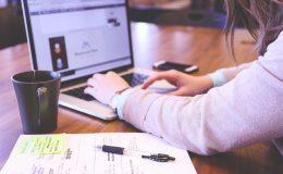 Personne travaillant sur son ordinateur, une table et un bloc se trouvent à sa gauche.